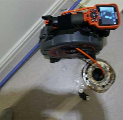 トイレ排水管にファイバースコープカメラ(管内カメラ)を差し込んで排水管内を見ている
